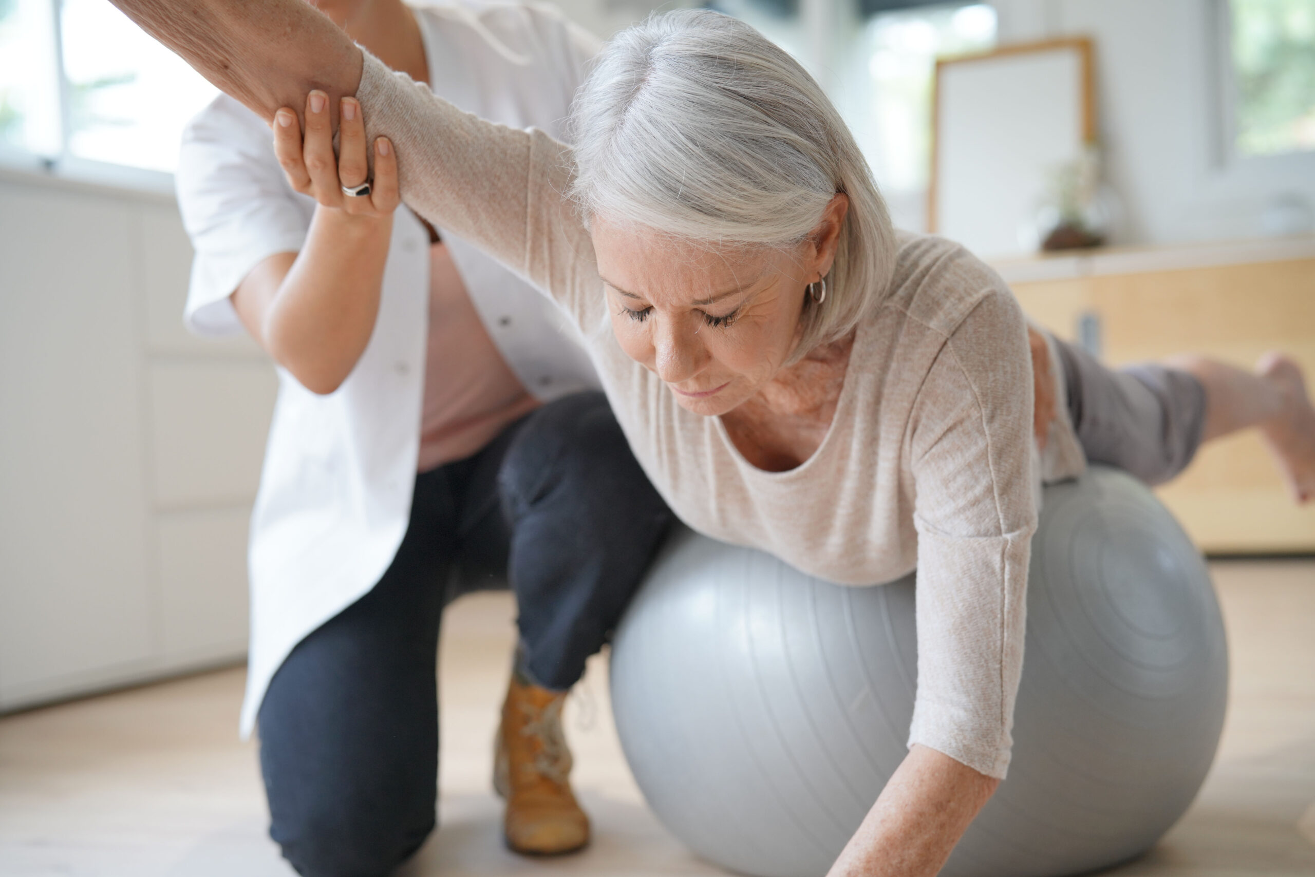 Senior,Woman,Exercising,With,Her,Physiotherapist,And,Swiss,Ball